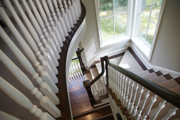 Beautiful interior curved staircase with dark wood and white spindles